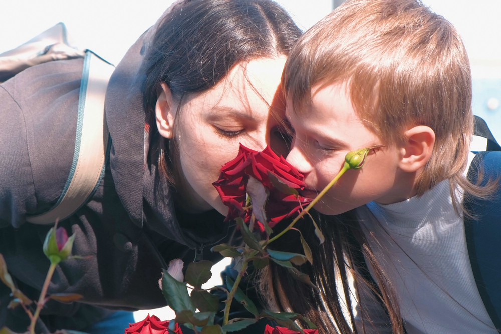 Mother and son together sniffing a rose(Vadim Zakharishchev)s