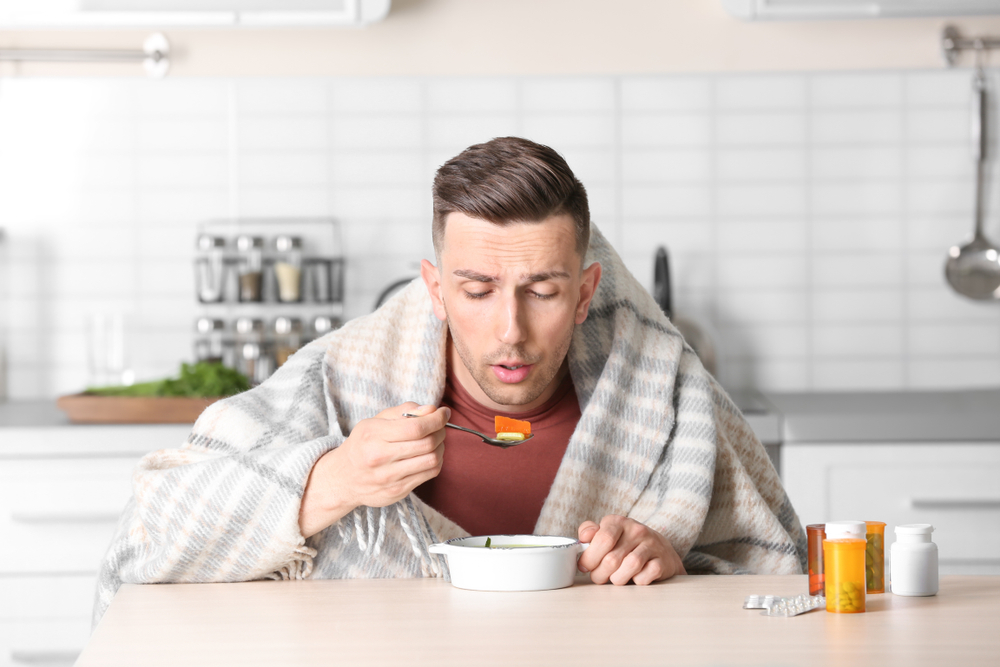 Sick young man eating broth to cure cold at table in kitchen(New Africa)s