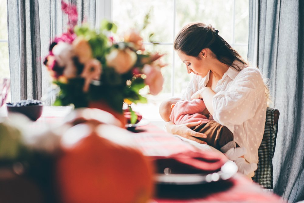 young-woman-with-long-dark-hair-breastfeeding-baby-AAT5WWM