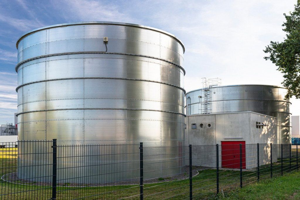 industrial-steel-silos-standing-on-the-factory-grounds-on-the-lawn-behind-the-fence-silos-silo_t20_NxKQNQ