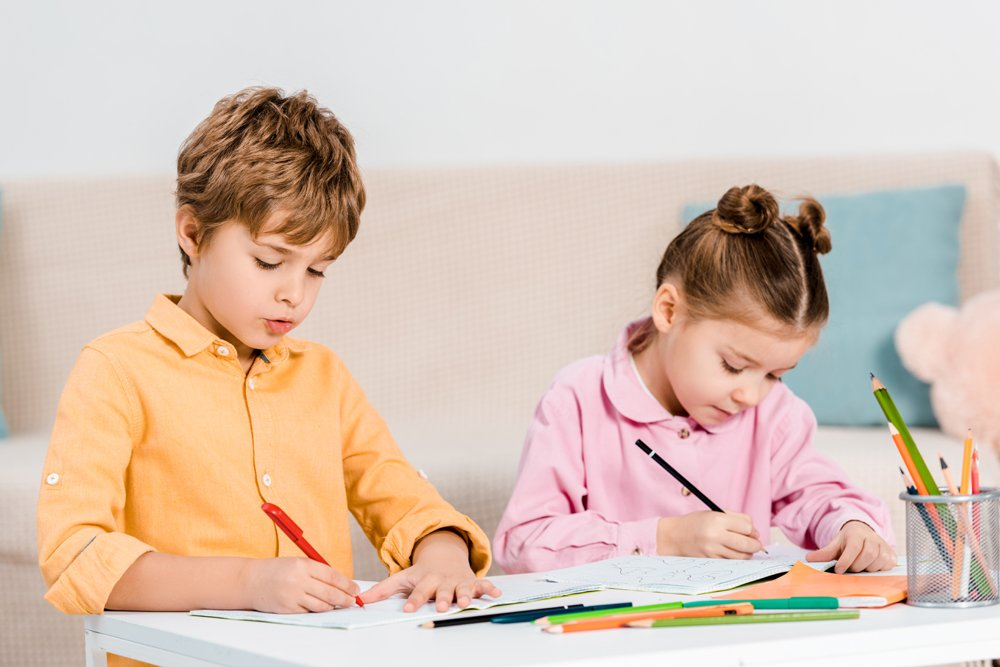 beautiful little children writing and studying together