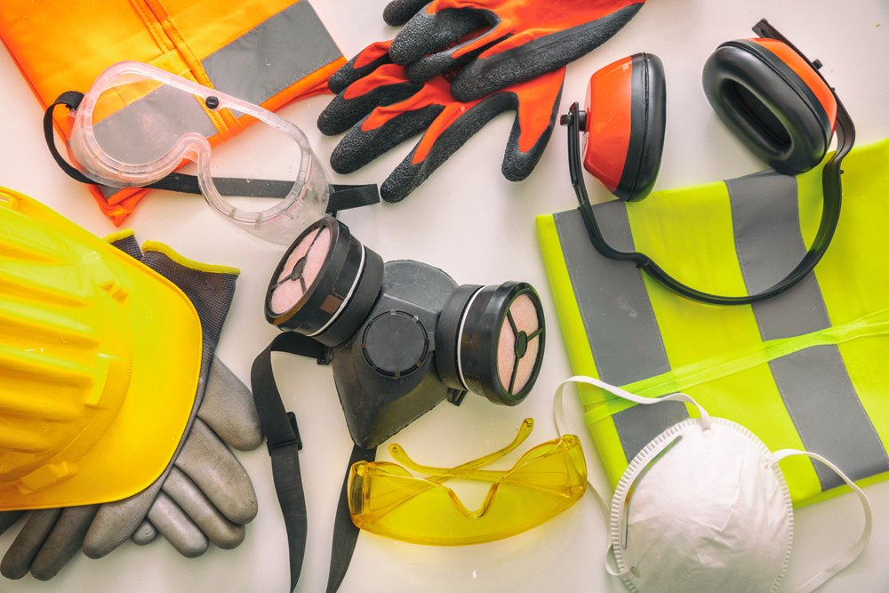 Work safety protection equipment flat lay. Industrial protective gear on white background, top view. Construction site health and safety concept