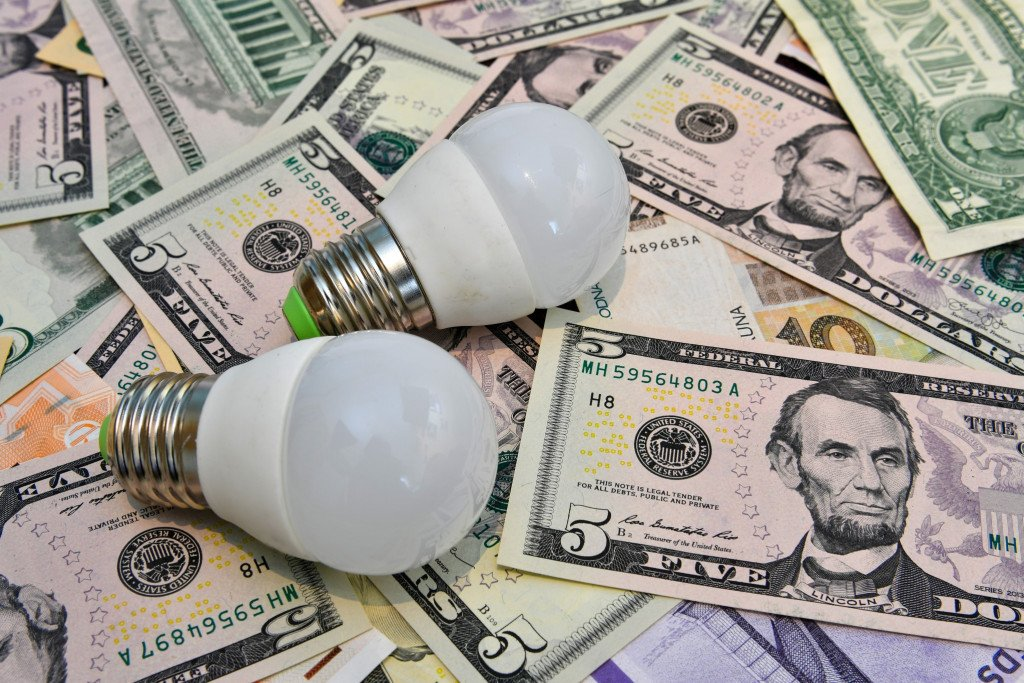 two-led-bulbs-in-the-background-of-different-countries-currency-notes-led-banknote-cash-energy-bulb_t20_kRg7nP